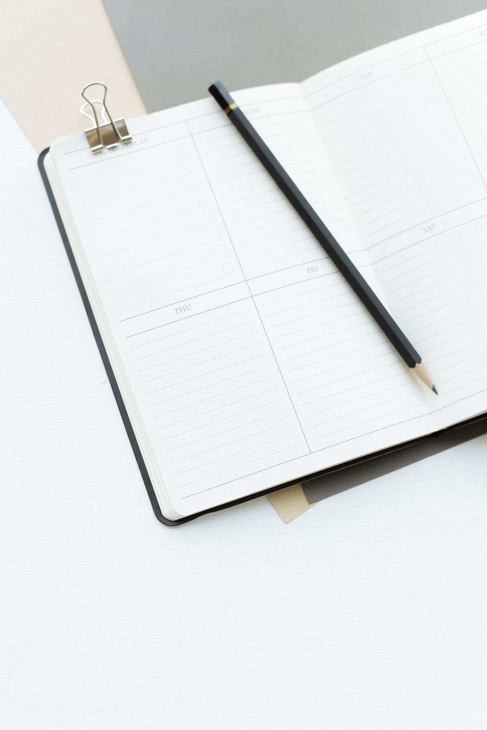 Das Bild zeigt ein geöffnetes Tage-Buch und einen Stift.